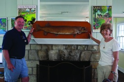 Kathryn Ford presents Sports Club director Richard Ulasewicz with a mounted 48-inch, 28-lb. muskellunge for display in the Sports Club. Ford's father caught the fish on Chautauqua Lake in 1962. Photo by Eve Edelheit.