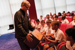 Brian Kushmaul, principal percussionist in the CSO and member of Ibis, shows students in Trinidad a cajon drum. Photo courtesy of Michelle Nunes.