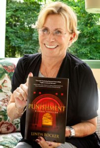 Linda Rocker poses on the front porch of her Chautauqua home with a copy of her book, Punishment. Photo by Michelle Kanaar.