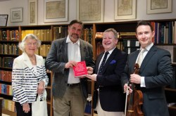 Carol Duehme, Jon Schmitz, Will Glover and David Strange pose in the Oliver Archives Center with a copy of The Journey of the English-Speaking Union. Photo by Adam Birkan.