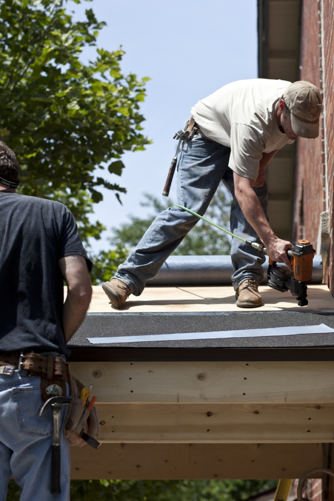 Benjamin Hoste | Staff PhotographerKirk Wyant of Southwest Construction, work on a new porch roof for the Oliver Archives Center on June 21. The construction project was one of many being completed in the week prior to the opening of the 2013 season.