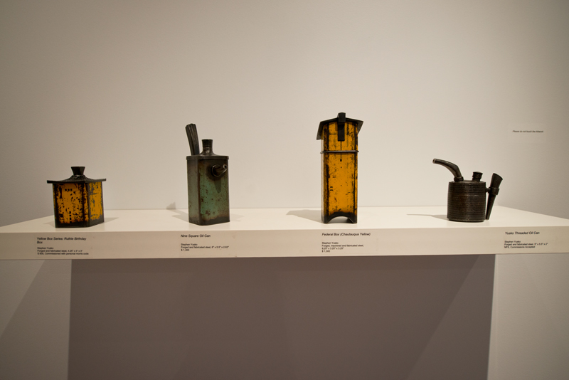 "Four of Stephen Yusko's pieces made of forged and fabricated steel — from left to right, ""Ruthie Birthday Box,"" ""Nine Square Oil Can,"" ""Federal Box (Chautauqua Yellow)"" and ""Yusko Threaded Oil Can"" — are displayed as part of the Fowler-Kellogg Art Center exhibition ""An Object of Beauty: Metal/Fiber/Glass"" through July 18."