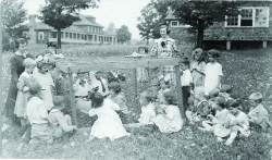 COURTESY OF CHAUTAUQUA INSTITUTION ARCHIVESIn a photo estimated to have been taken between 1920 and 1929, two teachers and a group of students from the Children's School observe animals in a coop. The Lodge (emergency hospital) appears in background to the left.