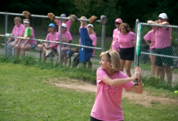 The Moms cheer on their teammate as she bats.