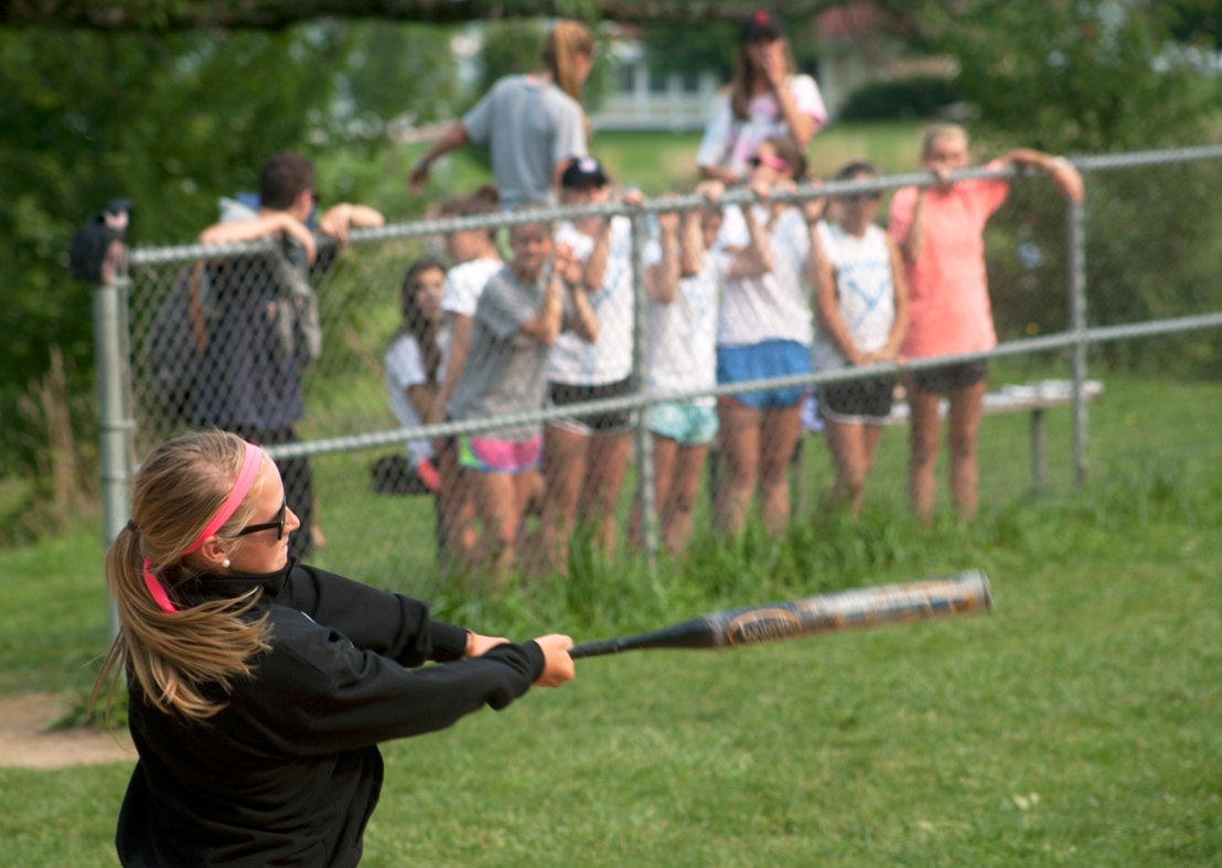 The Batgirls cheer on their teammate as she takes a swing during the softball championship game between the Batgirls and the Moms at Sharpe Field Thursday.