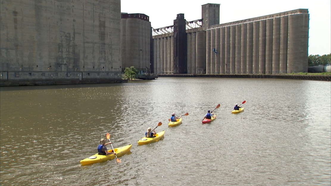 """Kayakers paddle past grain silos in Buffalo. David Rotterman, vice president of television production at WNED, will present the film """"If Water Could Talk"""" at 3:30 p.m. today in the Hall of Christ. (Provided photo)"""
