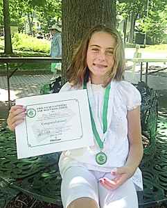 Ella Spremulli proudly displays her CLSC Young Readers medallion and certificate. She received the awards from the CLSC Veranda for reading 16 books from the program's historic list.