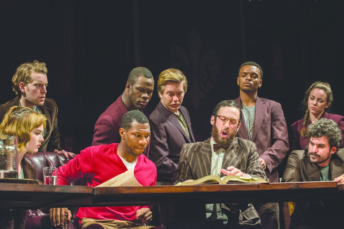 Henry, played by Jonathan Majors (seated, in red), is advised by his council in Chautauqua Theater Company's production of Henry V. The play continues its run through Friday in Bratton Theater. (Joshua Boucher | Staff Photographer)